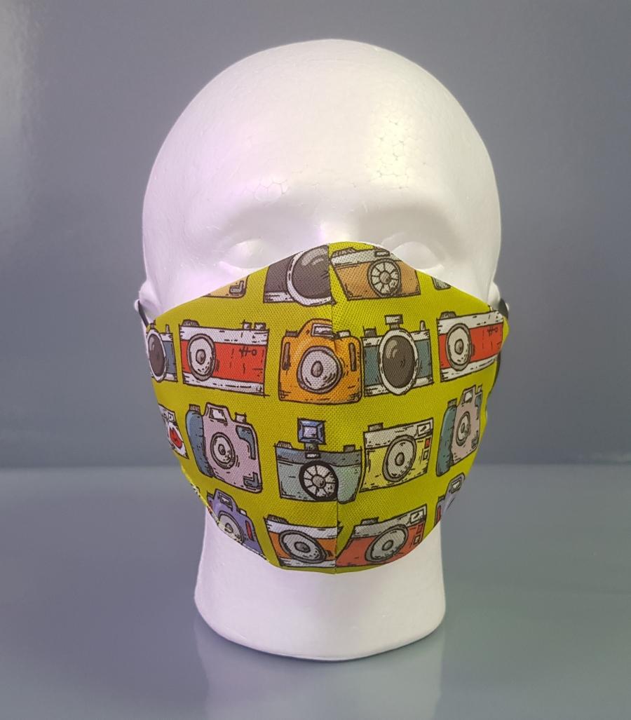 Mascarilla con estampado de cámaras fotográficas sobre fondo amarillo